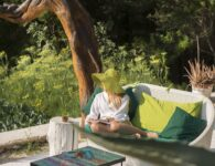 Young woman relaxing near the kitchen garden at Hotel Su Gologone in Oliena